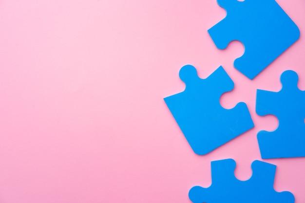 Pezzi di un puzzle blu sulla vista superiore del fondo di carta