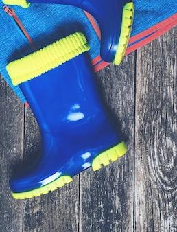 Stivali da pioggia blu e impermeabile. completo autunnale per bambini. disposizione piana, vista dall'alto. moda autunnale. impermeabile e stivali per bambini.