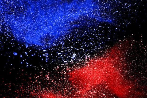 Esplosione di polvere di colore blu e rosso su sfondo nero