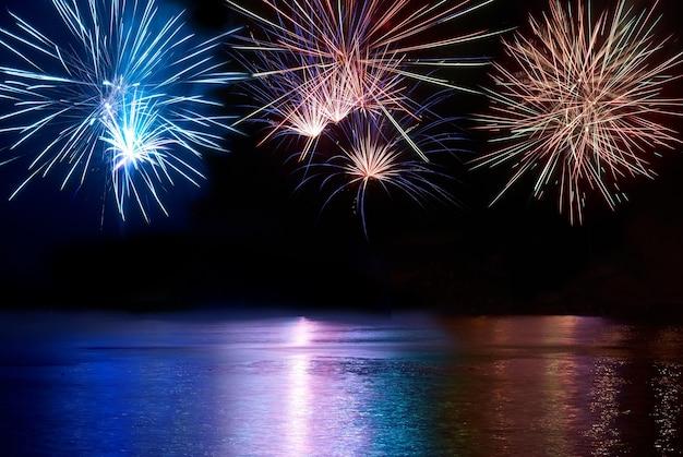 Fuochi d'artificio colorati blu, rossi e bianchi sopra il fiume. celebrazione delle vacanze.