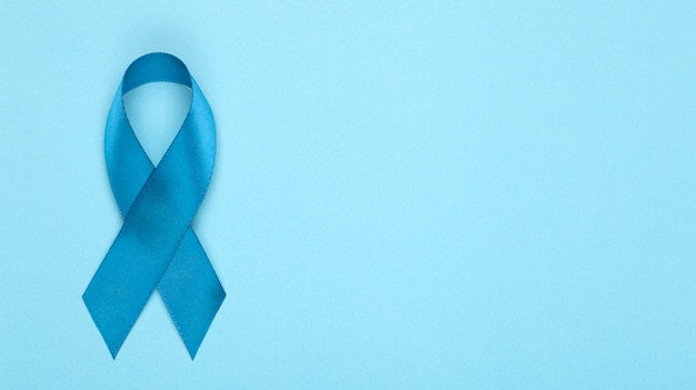 Nastro blu su sfondo. mese di sensibilizzazione sul cancro alla prostata. simbolo del nastro blu del mese mondiale del cancro alla prostata e concetto di assistenza sanitaria. copia spazio
