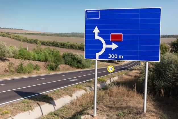 Segnale stradale blu che mostra la direzione vicino all'autostrada.