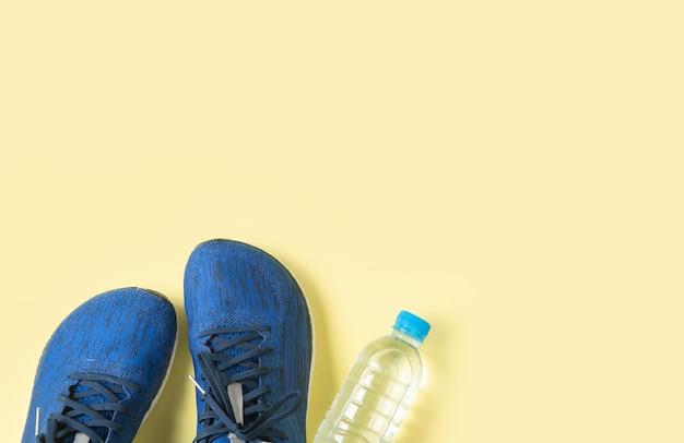 Scarpe da corsa e bottiglia blu di acqua su fondo giallo