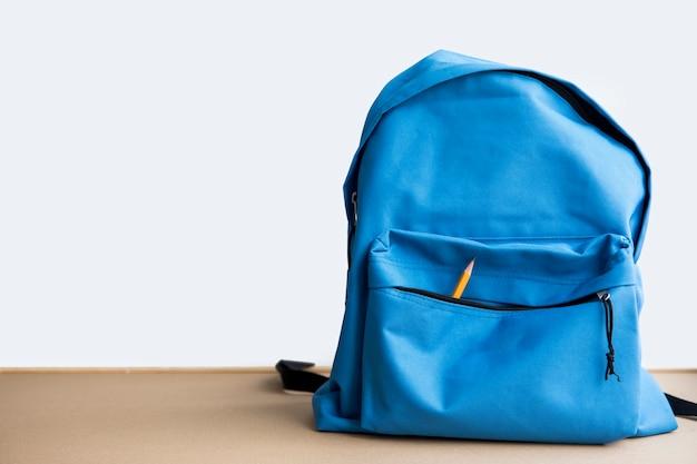 Zainetto blu con una matita in tasca