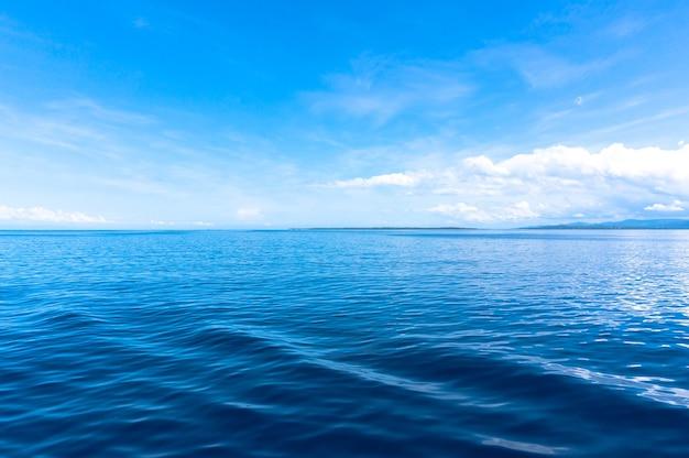 Orizzonte del cielo blu del mare blu con nuvole cumuliformi bianche