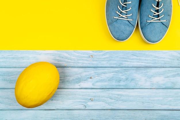 Scarpe blu e un melone stanno su uno sfondo blu e giallo misto isolato.