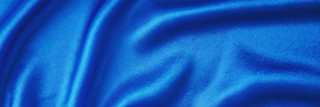 Sfondo di seta blu con pieghe. struttura astratta della superficie satinata increspata Foto Premium