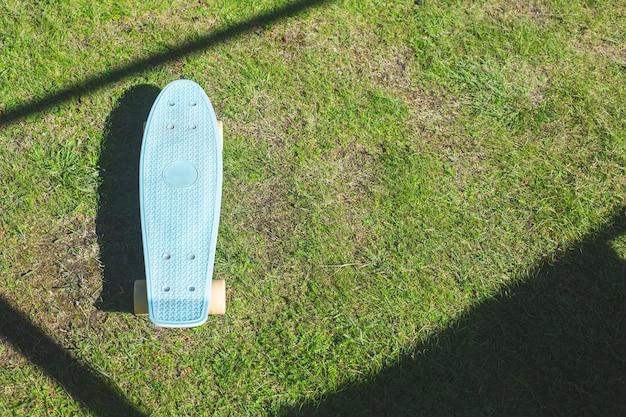 Uno skateboard blu su un prato verde, vista dall'alto. stile di vita attivo, attrezzature sportive. un proiettile per acrobazie, salti