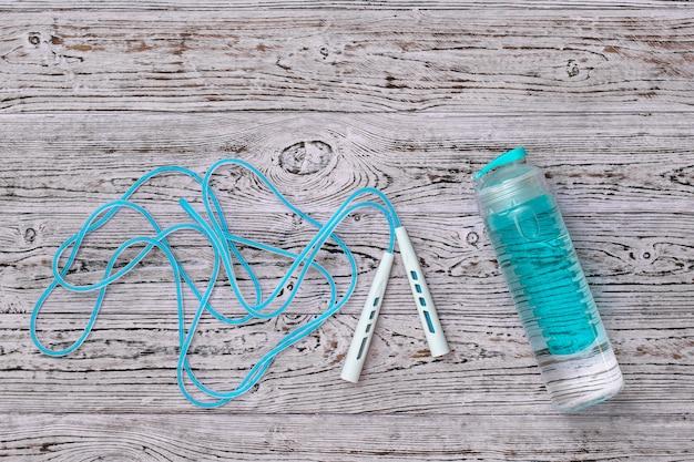 Corda per saltare blu e bottiglia d'acqua blu su superficie di legno