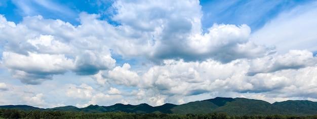 Sfondo azzurro del cielo con piccole nuvole. panorama, ampio panorama del cielo con nubi cumuliformi sparse, cielo blu e nuvola con albero di prato. sfondo paesaggio semplice per poster estivo.