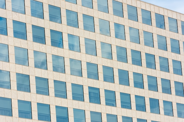 Cielo azzurro e nuvole riflesse nelle finestre di un moderno edificio per uffici