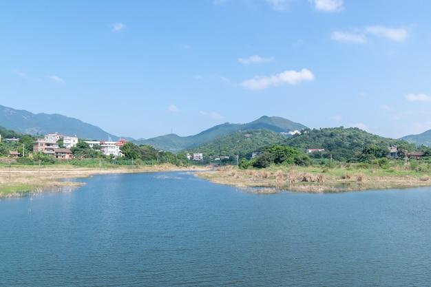Le montagne e gli alberi verdi del cielo blu circondano il lago