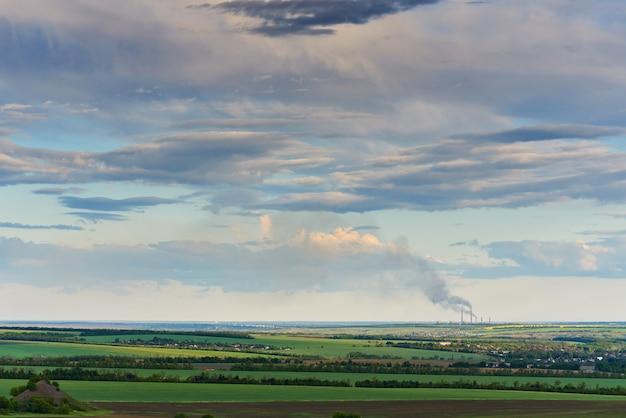 Cielo blu con nuvole sopra i campi verdi e una centrale termoelettrica con un camino fumante.