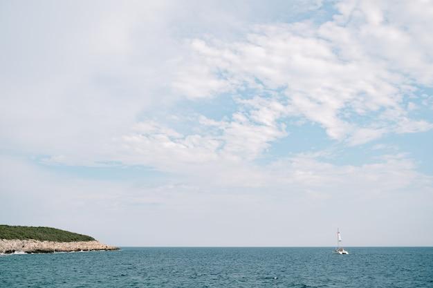 Cielo blu con nuvole bianche catamarano galleggia sul mare in lontananza