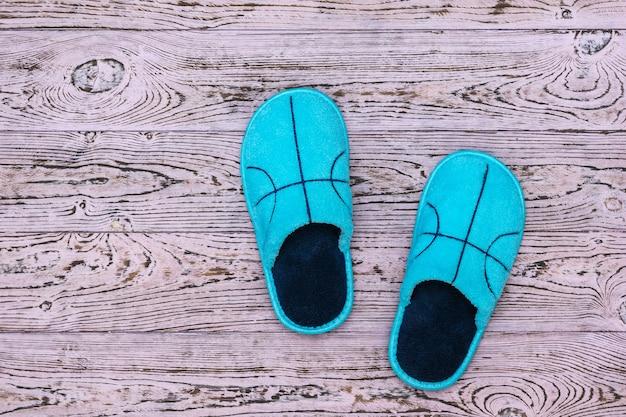 Pantofole blu su una bella parete in legno. scarpe comode da casa. lay piatto.