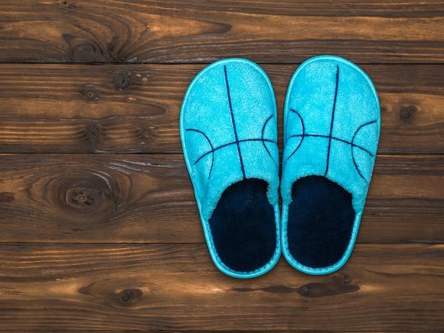Pantofole blu sul pavimento in legno marrone scuro