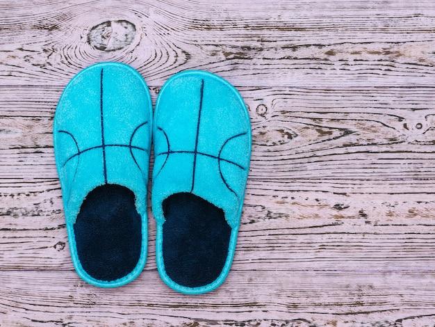 Pantofole blu su un pavimento di legno rosa