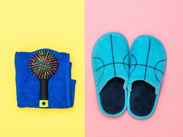 Pantofole blu, asciugamano e pettine sulla superficie rosa e gialla
