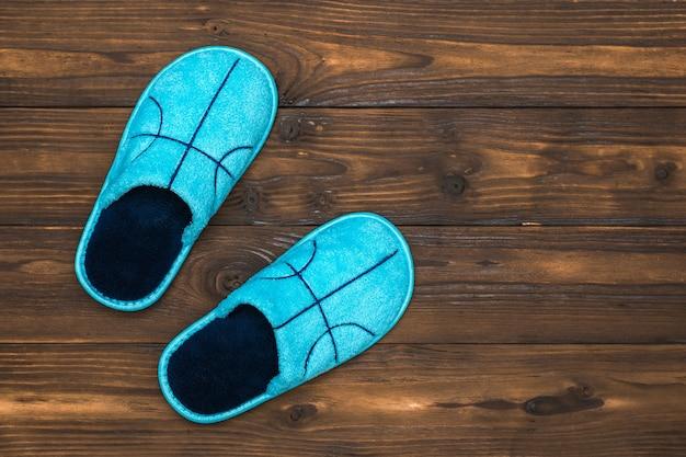 Pantofole blu su legno. scarpe comode da casa. lay piatto.