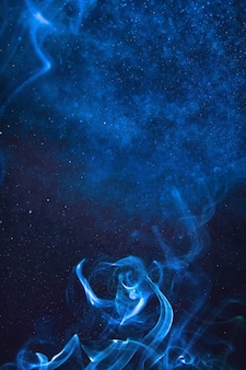 Fumo blu e spruzzi d'acqua su sfondo nero
