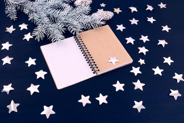 Il taccuino bianco dell'urto del ramo dell'albero di natale delle stelle blu segna i simboli