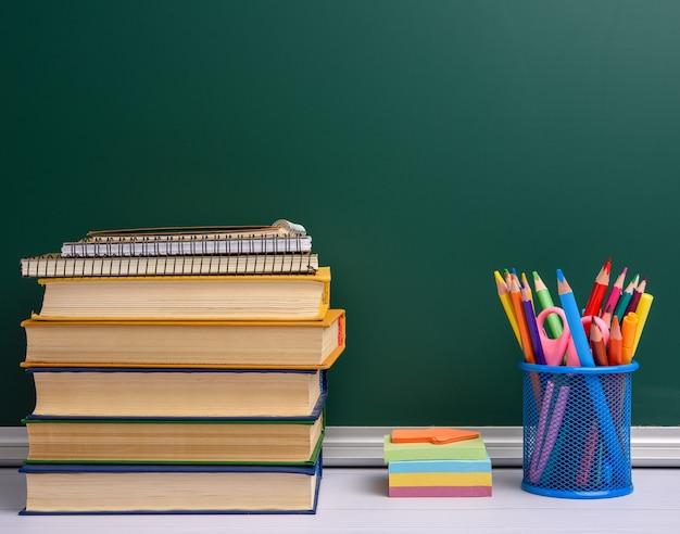 Vetro blu della cancelleria con le matite e le penne di legno multicolori, fondo verde della lavagna, spazio della copia