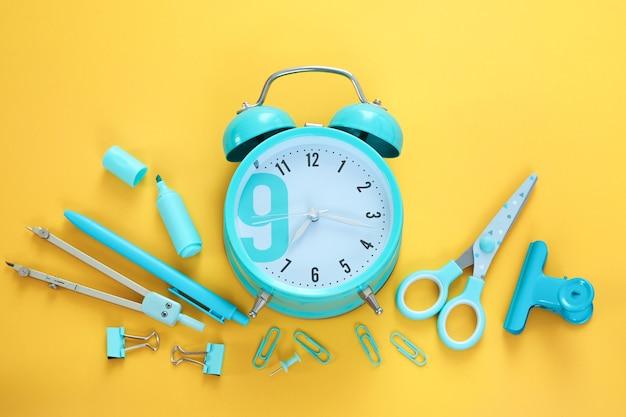 Articoli di cancelleria blu e sveglia su sfondo giallo. materiale scolastico, tempo a scuola, sveglia al mattino. flatlay colorato, vista dall'alto. pennarello, penna, graffette, forbici.