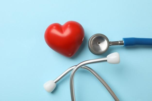 Stetoscopio e cuore blu sulla superficie blu