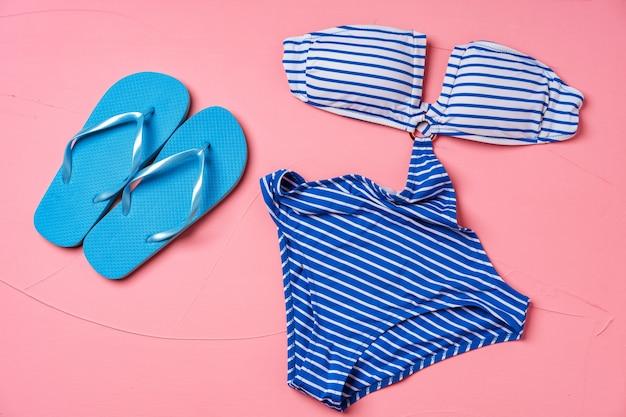 Monokini a righe blu con infradito blu su sfondo rosa