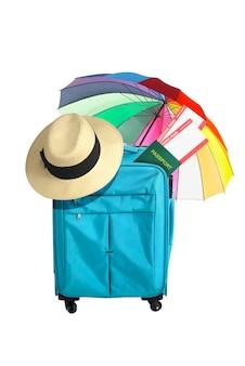 Valigia blu, cappello, biglietto e passaporto con ombrello isolato su sfondo bianco