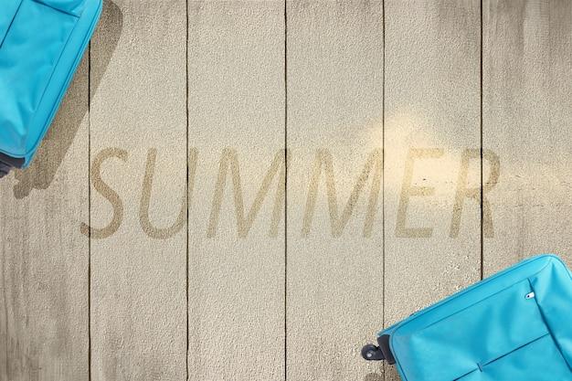 Valigia blu sul pavimento di legno con il testo dell'estate