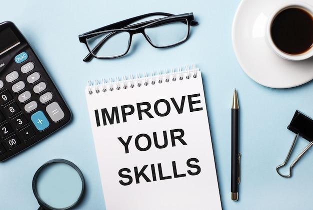 Su una superficie blu, occhiali, calcolatrice, caffè, lente d'ingrandimento, penna e taccuino con il testo migliora le tue abilità