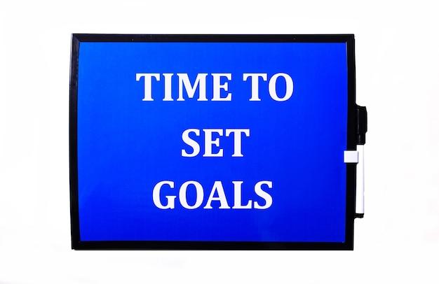 Su una superficie blu una scritta bianca time to set goals