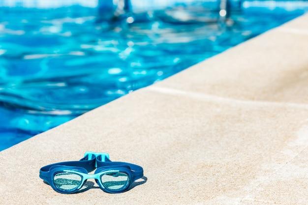 Occhialini da nuoto blu sul bordo della piscina, nell'angolo in basso a sinistra, con l'acqua blu in lontananza