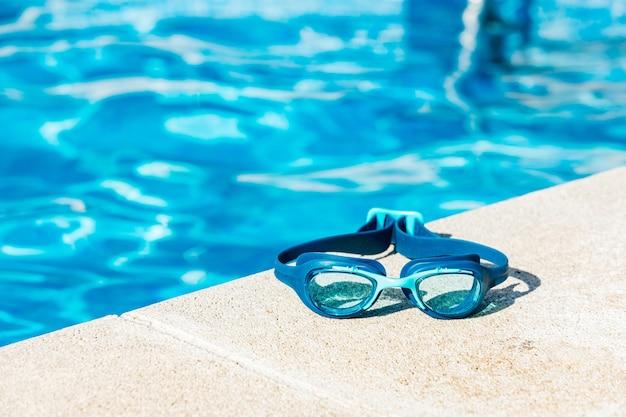 Occhialini da nuoto blu sul bordo della piscina, nell'angolo in basso a destra, con l'acqua blu in lontananza