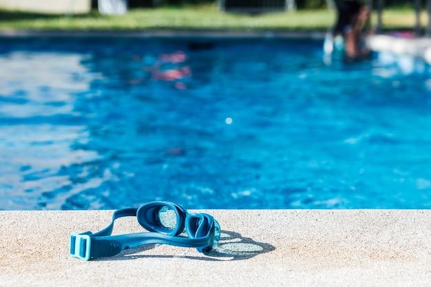 Occhialini da nuoto blu sul cordolo in pietra della piscina con acqua blu a distanza