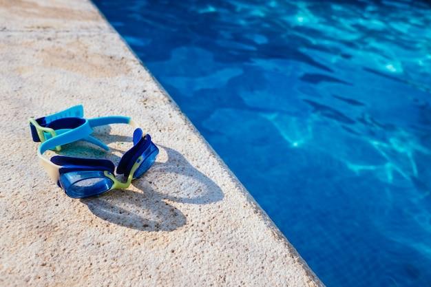 Occhiali da piscina blu illuminati dal sole estivo sul bordo di una piscina privata.