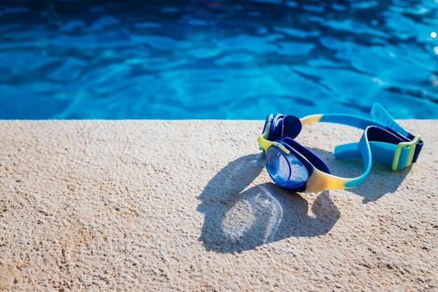 Occhialini da piscina blu illuminati dal sole estivo sul bordo di una piscina privata