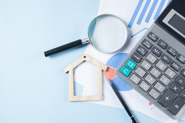 Su un tavolo blu una calcolatrice, statistiche, una penna e una casa