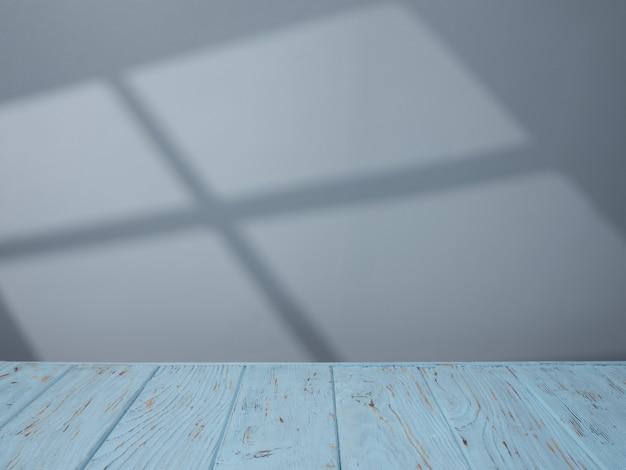 Piano del tavolo blu sullo sfondo del muro con luce dalla finestra
