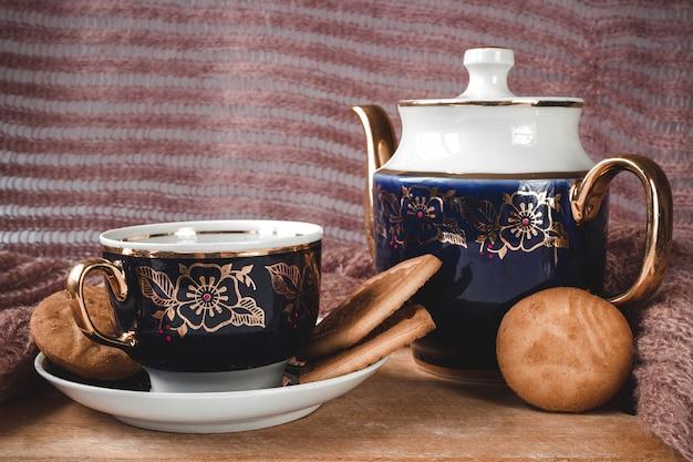 Teiera blu con tazza e piattino su un vecchio tavolo in legno con biscotti.