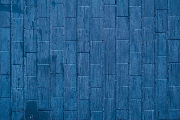 Fondo blu delle mattonelle con le macchie della pittura, struttura scura della parete in bagno.