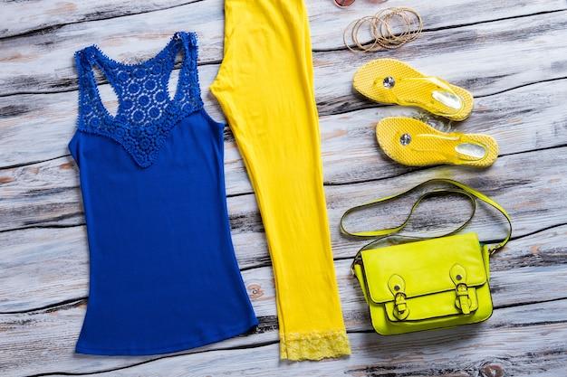 Borsa superiore blu e lime. canotta con infradito. abbigliamento e calzature luminosi da ragazza. nuova merce su vetrina bianca.