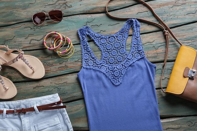 Top blu e occhiali da sole. borsa marrone e arancione. accessori alla moda nel negozio di marca. bracciali da donna sul tavolo di legno.