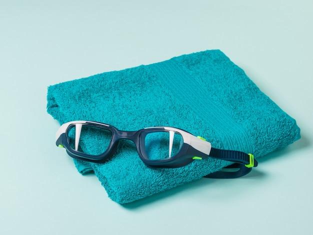 Asciugamano blu e occhialini da nuoto su sfondo chiaro. accessori per il nuoto in piscina.