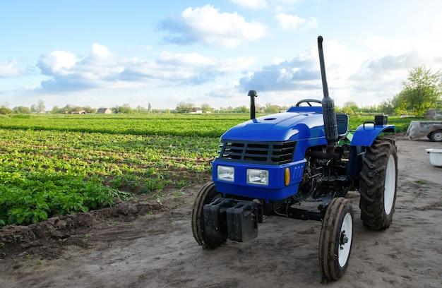 Trattore blu senza conducente vicino a un campo agricolo organizzazione di macchine e tecnologie agricole