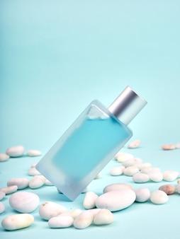 Bottiglia di profumo trasparente blu, vetro smerigliato, su sfondo blu e pietre accanto.