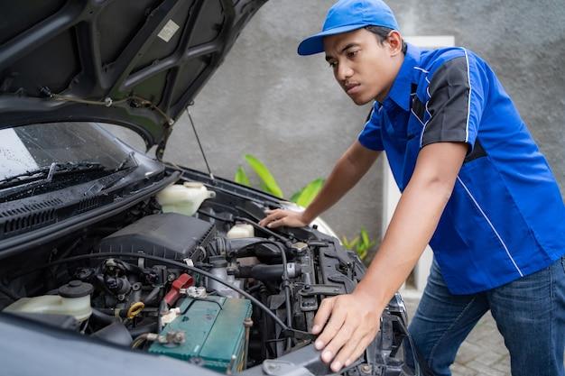 Lavoratore uniforme blu dell'ingegnere automobilistico che esamina il motore dell'automobile