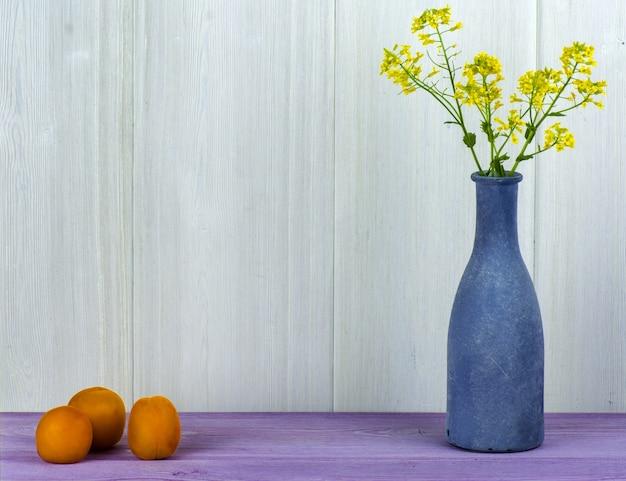 Un vaso blu con un campo di fiori gialli e albicocche sul tavolo.