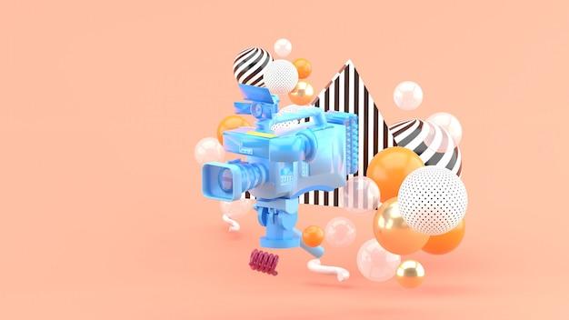 Una videocamera blu circondata da palline colorate sul rosa. rendering 3d